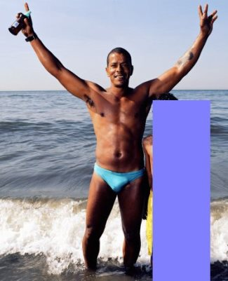 black guy wearing speedo - random hunk on the beach